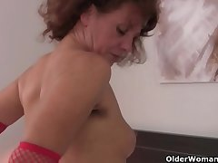 Hairy grandma Inge wide red stockings is fingering the brush full bushed pussy